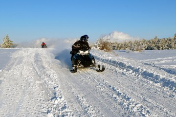mans goes on a snowmobile on snow road
