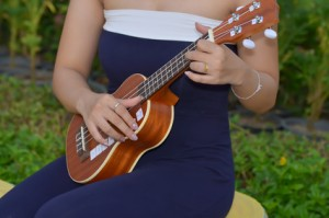 young woman plays ukulele thailand